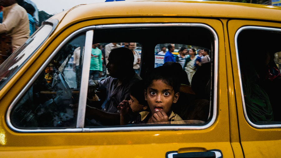 Indian kid is sitting in the taxi and looking at the camera ASIA Asian  India Indian Kolkata Looking At Camera Stunning Taking Photos Adorable Boys Car Childhood Cute Headshot Kid Looking At Kid Smiling Land Vehicle Looking At Camera Public Transportation Sitting Surprise Transportation Window Young Adult
