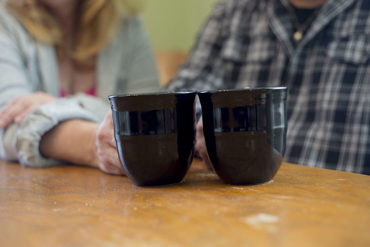 Midsection of couple holding coffee cup