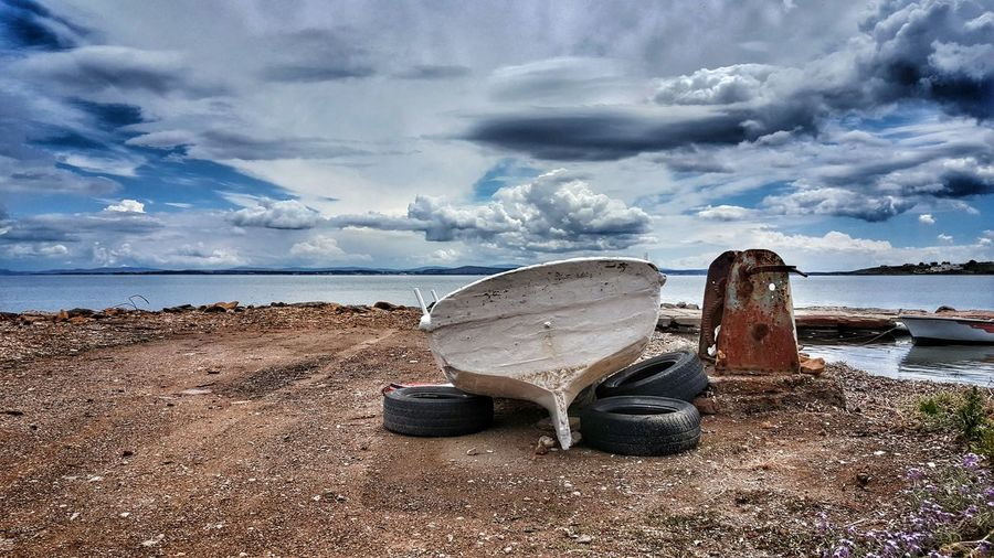 Boat And Tires On Lakeshore Against Sky