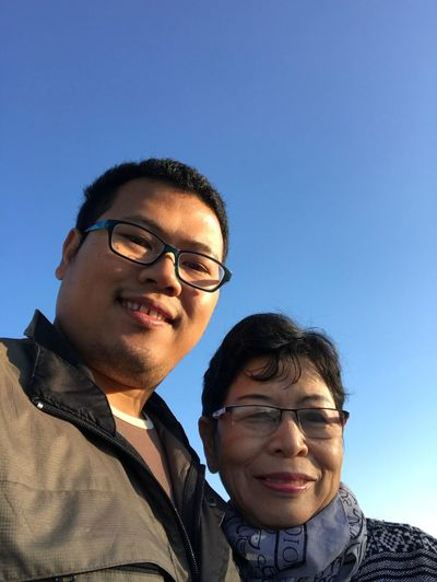 Portrait of mother and son against clear blue sky
