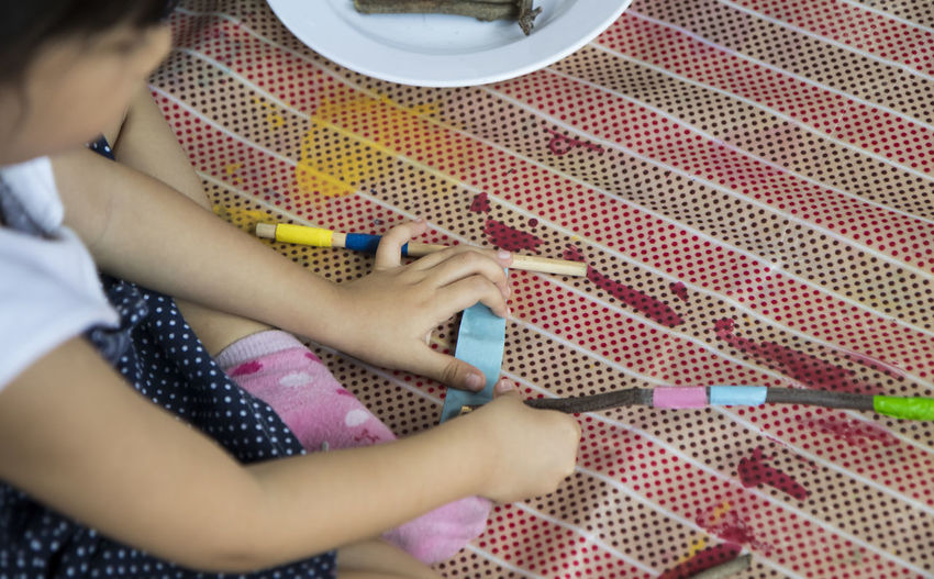 High angle view of girl holding stick while sitting on floor