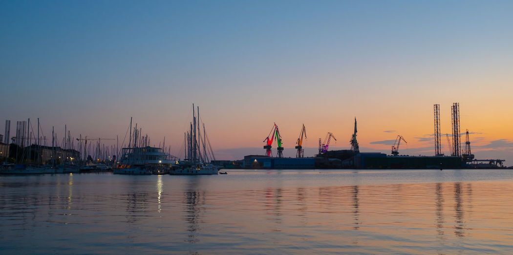 Sailboats moored in sea against clear sky during sunset