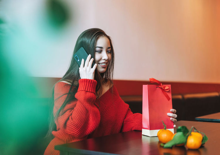 asian woman in red clothes using mobile with gift bag in cafe, celebrating chinese new year