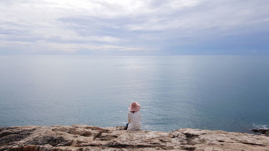 Rear View Of Woman Sitting On Cliff By Sea Against Cloudy Sky
