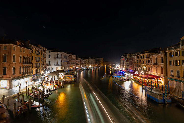 Canal amidst illuminated buildings in the city of venice at night