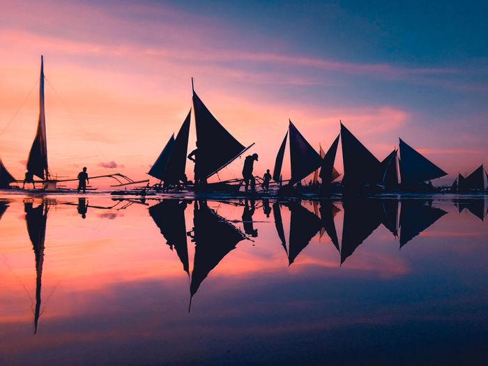 Silhouette tall ship in sea against orange sky