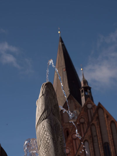"""Church and Fish Sculpture (""""Socialistic Realism"""") Church Architecture Built Structure Clouds And Sky Day Fish Flountain Low Angle View No People Outdoors Sculpture Sky Statue"""