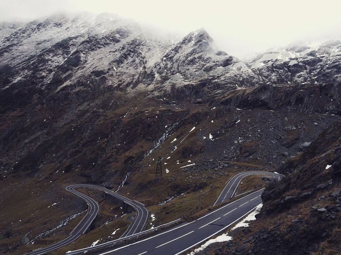Winding road against rocky mountains