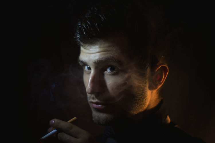Close-Up Of Man Smoking Cigarette In Darkroom