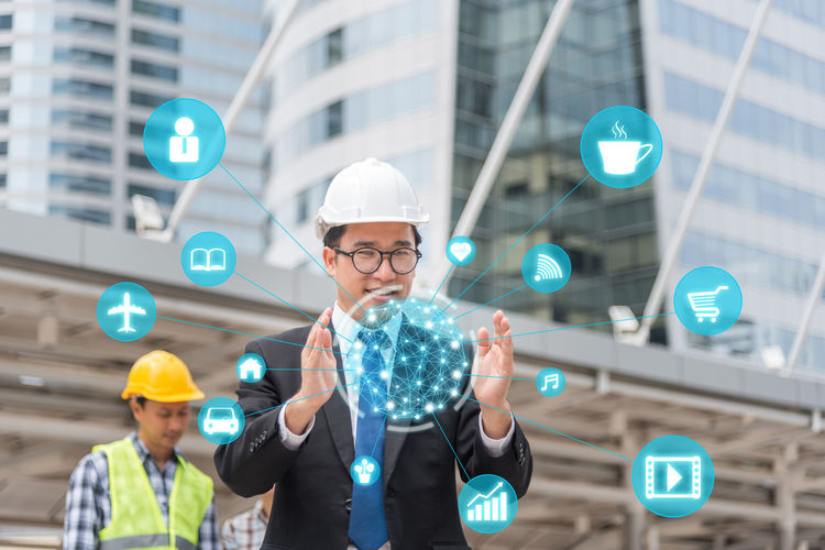 Digital Composite Image Of Engineer Standing By Various Icons Against Building