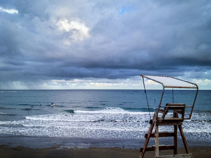 Lifeguard chair by sea against cloudy sky