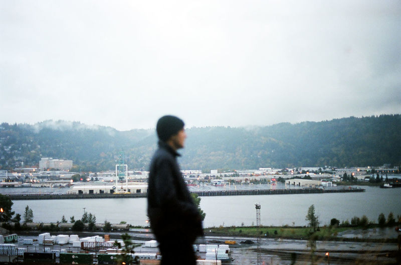 Man standing by river in city against sky