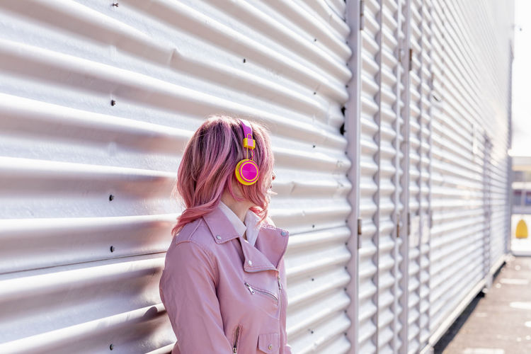 Portrait of woman standing against pink wall
