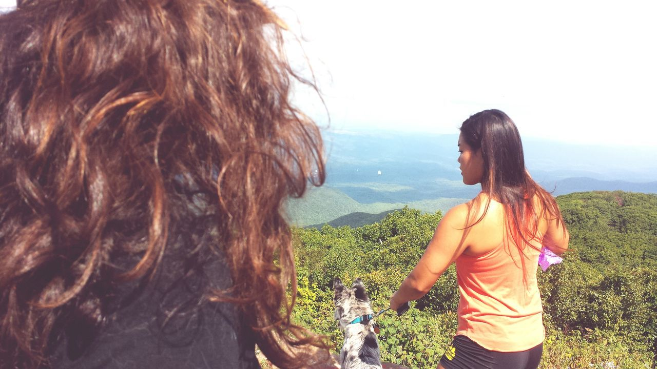 real people, rear view, leisure activity, lifestyles, casual clothing, togetherness, two people, long hair, brown hair, nature, women, outdoors, standing, friendship, day, backpack, mountain, bonding, tree, beauty in nature, young women, sky, young adult, people