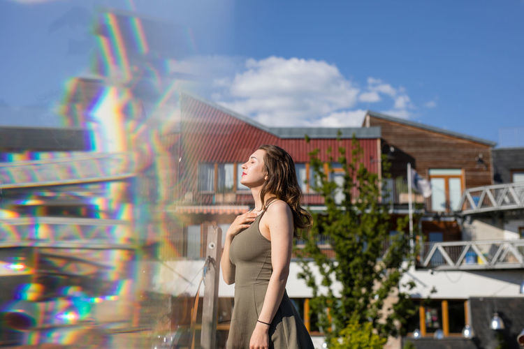 Double exposure of young woman and buildings during sunny day
