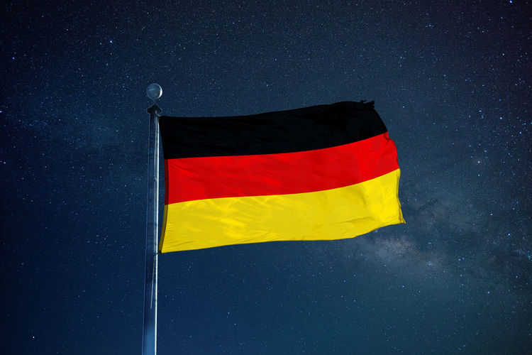 Low angle view of german flag against star field sky