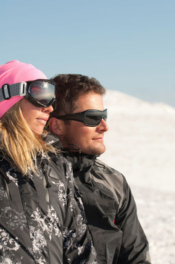 Smiling Mid Adult Couple Looking Away On Snowcapped Mountain