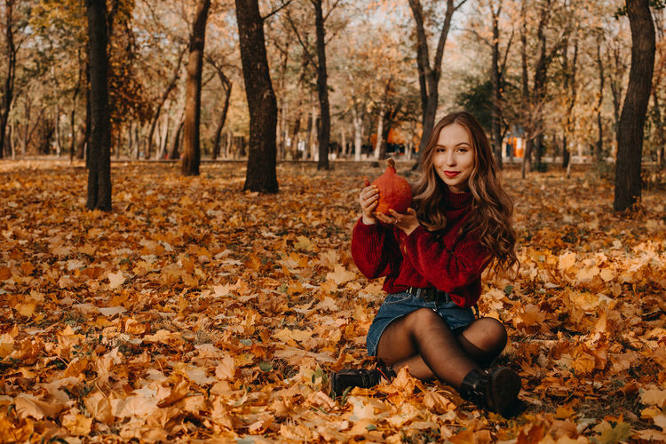 Young woman with dry leaves on ground during autumn