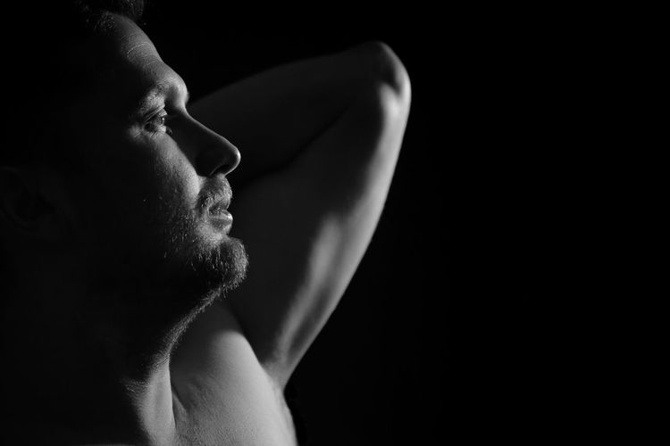 Close-up of shirtless man standing against black background