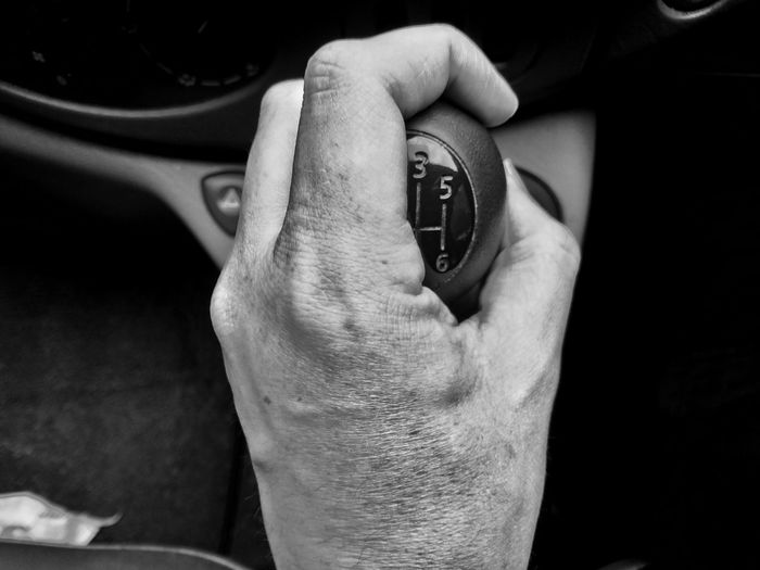 Close-up of hand holding gearstick in car