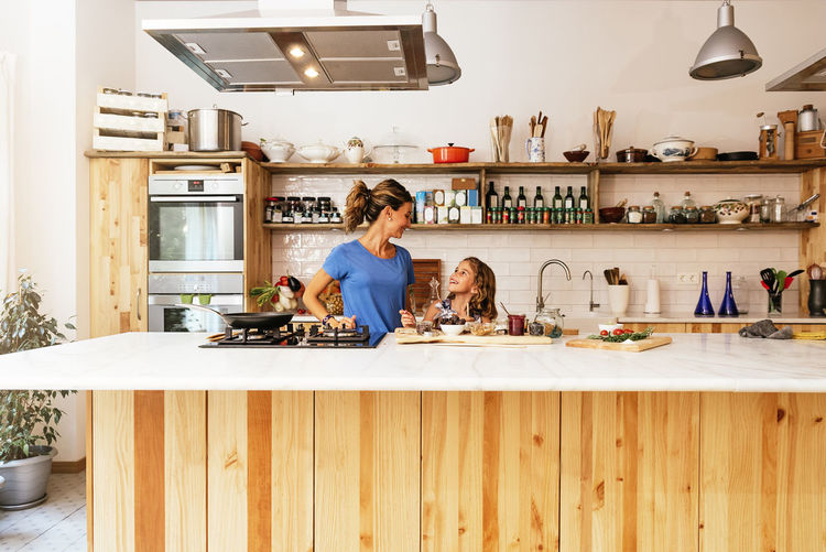 Smiling mother and daughter preparing food in kitchen at home