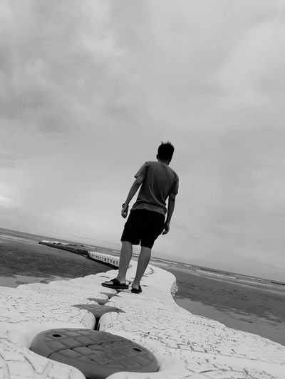 Tilt Shot Of Man On Walkway At Beach Against Cloudy Sky
