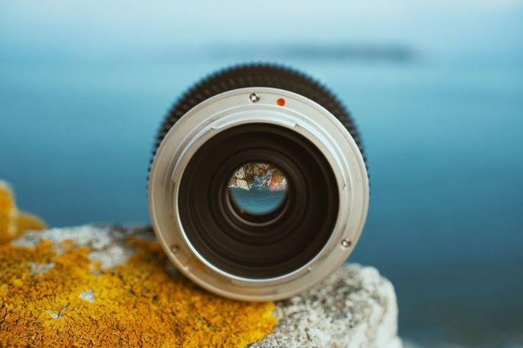 Close-up of camera lens against sea on rock