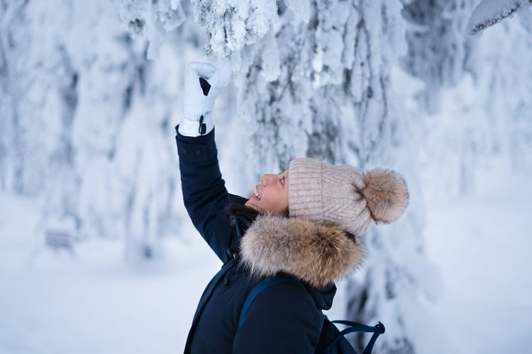 Woman touching snow covered tree during winter