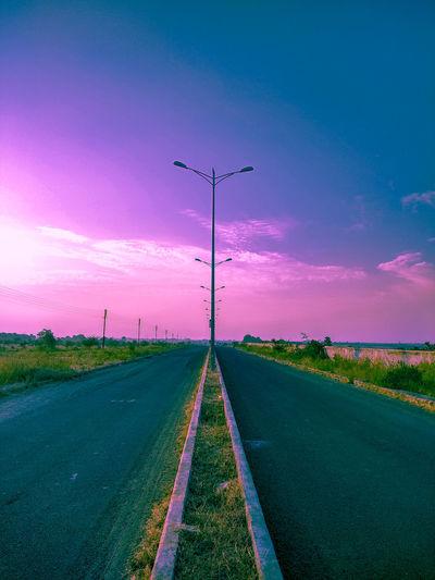 Street light on road against sky during sunset