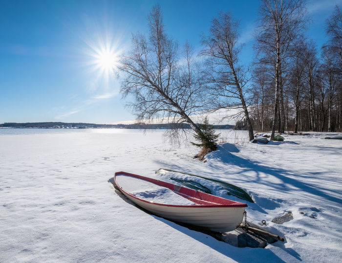 Bright winter day with sunlight, boat and sun beams at lake in Finland Winter Snow Cold Temperature Sky Nature Land Sunlight Day Outdoors Nautical Vessel Boat Finland Lens Flare Beauty In Nature Tree Tranquil Scene No People Sun Tranquility Scenics - Nature Ray Sunbeam Landscape Bright Blue Sky