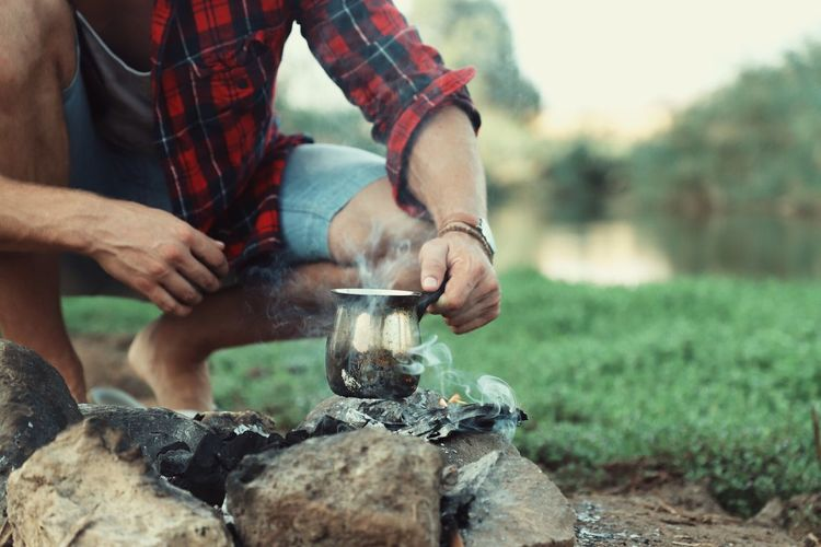 Midsection of man boiling drinking water on campfire