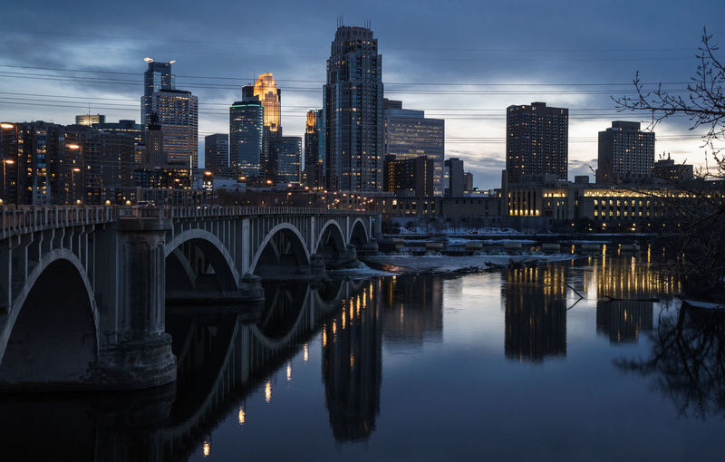 Bridge over river by illuminated buildings against sky at dusk