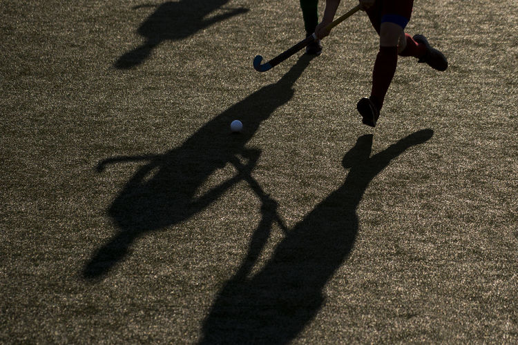 Low section of players playing hockey on field