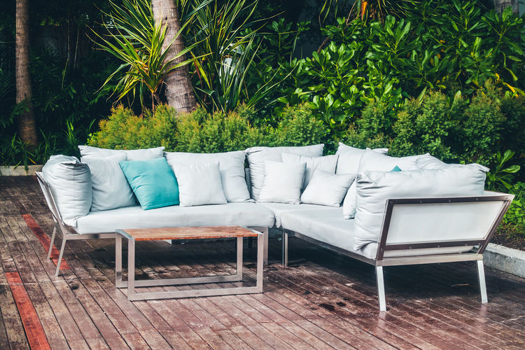 Absence Chair Coffee Table Comfortable Cushion Day Electric Lamp Empty Flooring Furniture Green Color Growth Luxury Nature No People Outdoors Pillow Plant Relaxation Seat Sofa Stuffed Tree Wood