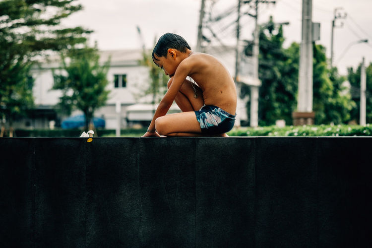 Side View Of Shirtless Boy Sitting Outdoors
