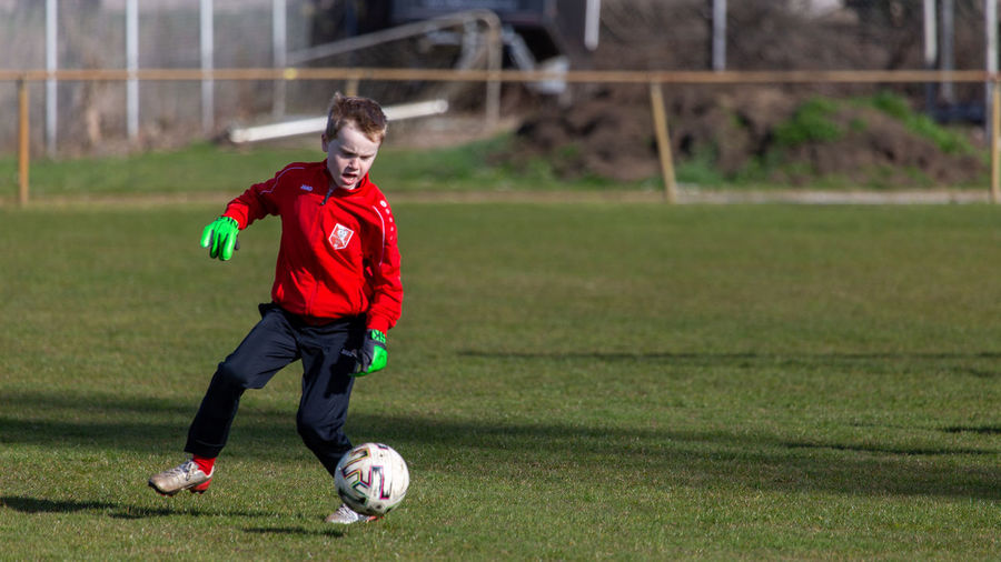 Full length of boy playing soccer ball on grass