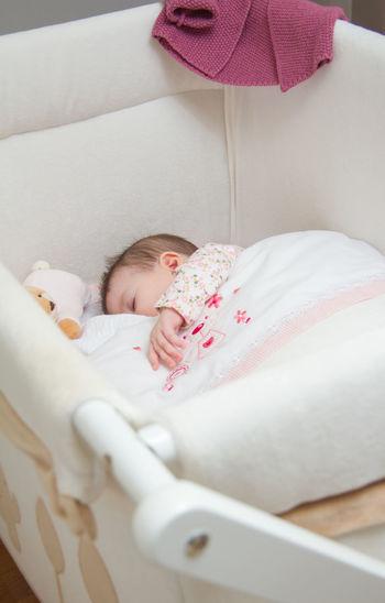 Baby girl sleeping in crib at home