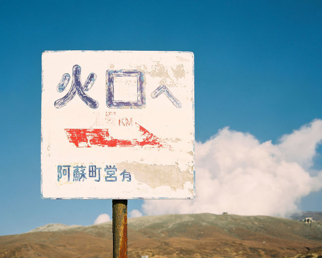 A sign directs visitors to the crater of Mount Aso in Kyushu, Japan. KYUSHU Mount Aso Steam Travel Adventure Blue Communication Crater Day Exploration Fumes Geological Medium Format Nature No People Outdoors Road Sign Sky Text Volcano 九州 日本 火口 火山 阿蘇山