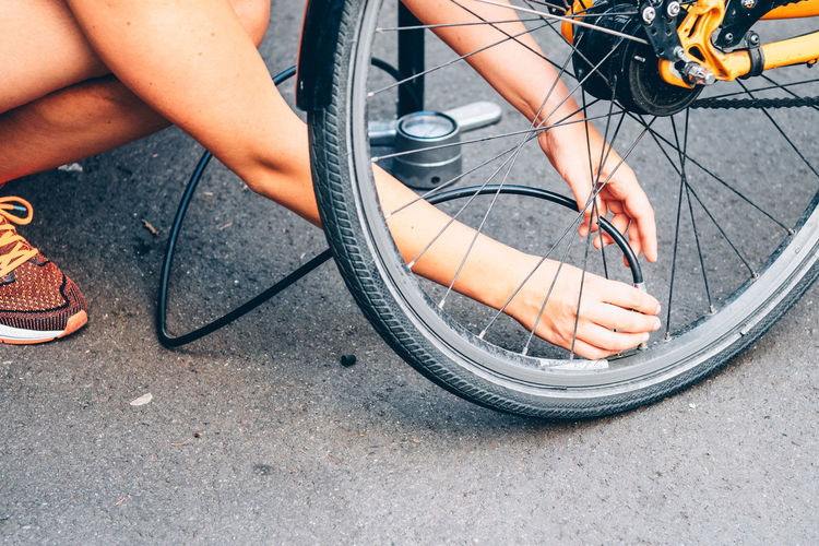 Cropped image of man pumping bicycle tire on street
