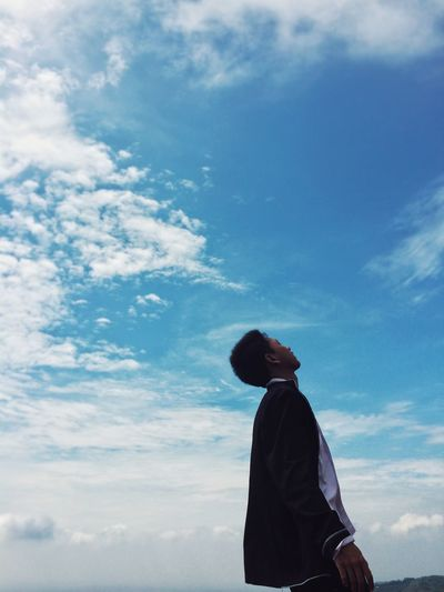 Low angle view of man with closed eyes standing against sky