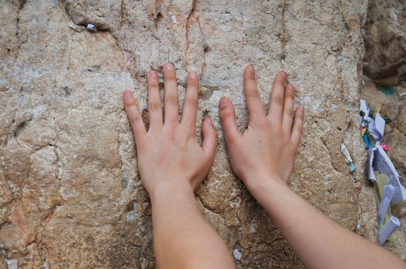 Close-up of hands touching rock formation