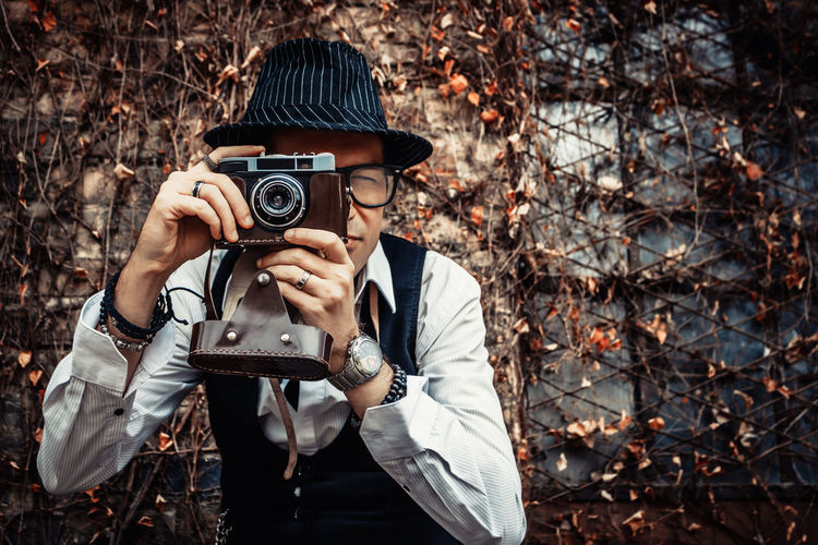 Retro-styled photographer taking picture with analog photo camera outdoors.