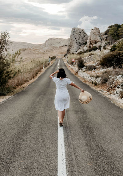 Rear view of young woman in white dress standing on road. summer, wanderlust, travel.