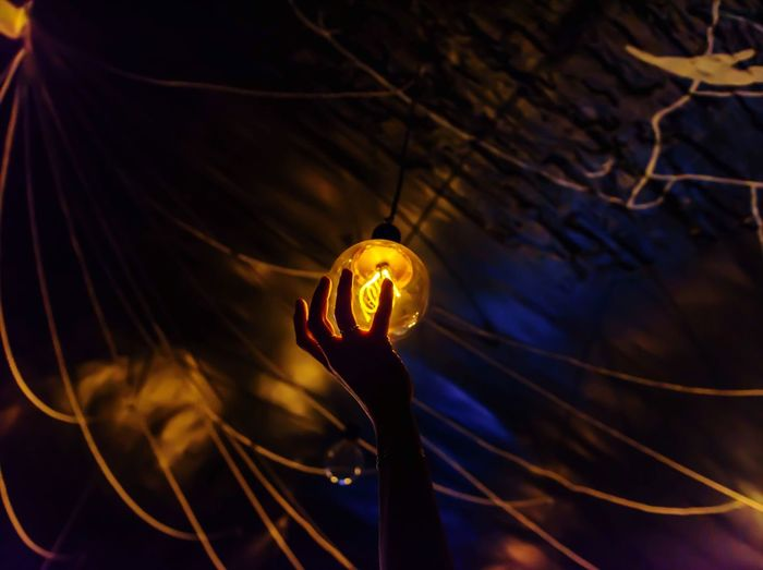 Cropped Hand Touching Illuminated Light Bulb