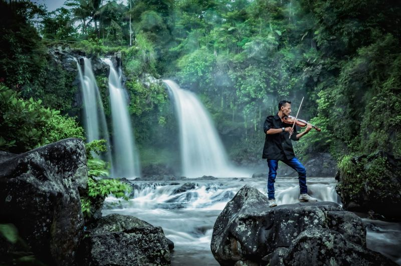 Man playing violin while standing on rock against waterfall in forest