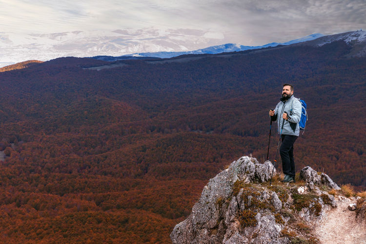 Full length of man standing on rock against mountains