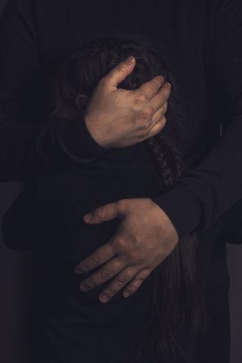 Close-up of man holding hands over black background