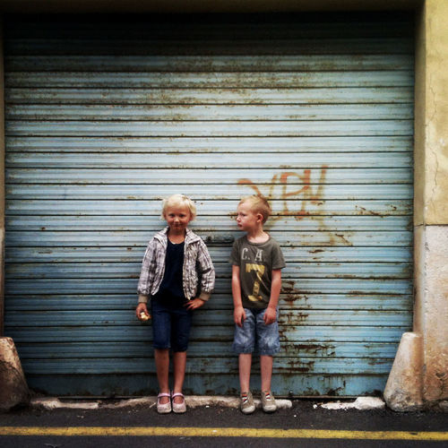 Two children standing on the street outside a garage. Casual Clothing Child Childhood Innocence Portrait Sibling Street Vacation