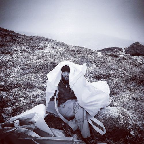Portrait of man covered with plastic on mountain during winter