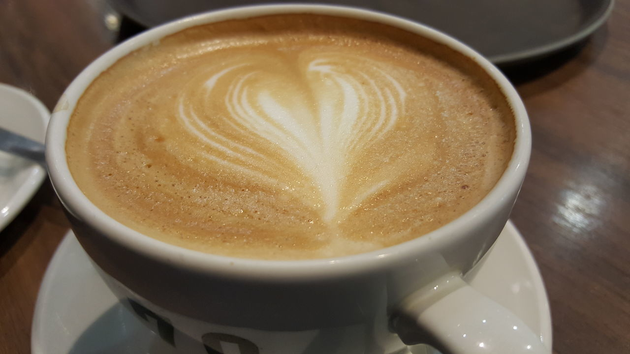 coffee cup, coffee - drink, frothy drink, cappuccino, drink, refreshment, froth art, food and drink, latte, table, close-up, indoors, froth, freshness, high angle view, no people, focus on foreground, saucer, cafe, mocha, day